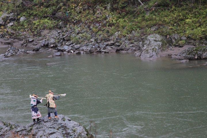 イナウを川に投入する様子